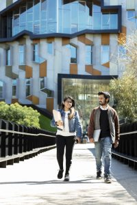 DC35747, Campus photography for International market, boardwalk, Sylvia Walton building, Lovee Jain (blue denin jacket) and Pranith Chander Kyatham (jacket with brown sleeves)